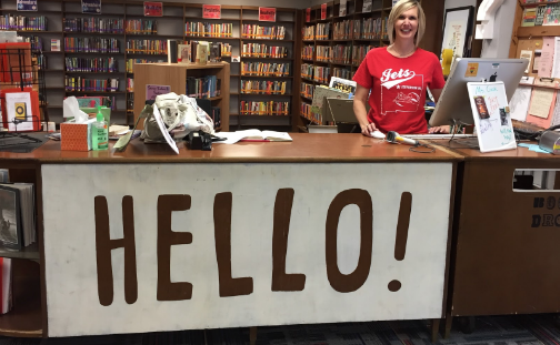 Picture of Ms. Cook by the circulation desk